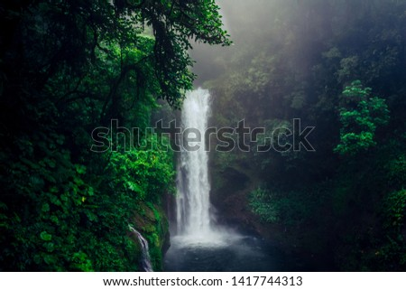Beautiful and wild waterfall in the middle of the green jungle in Costa Rica.  #1417744313