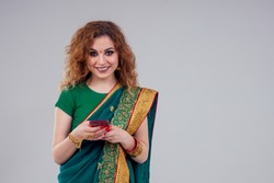 beautiful and young indian business woman in traditional india sari working using a smartphone phone.asian student girl remote work freelancer