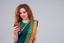 beautiful and young indian business woman in traditional india sari working using a smartphone phone.asian student girl remote work freelancer.