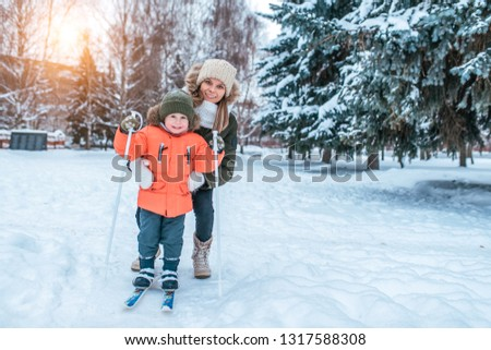 d057a0e53af68 Beautiful and young mother teaches to ski