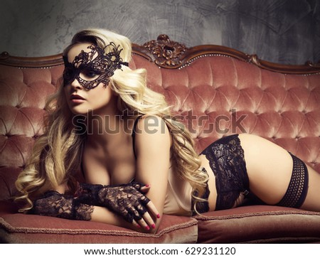 Beautiful and young woman posing in sexy lingerie and Venetian mask on red sofa. Vintage interior and retro background.
