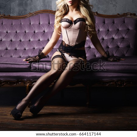 17e65e362 Beautiful and young woman posing in sexy lingerie and Venetian mask on  violet sofa. Vintage