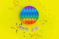 beautiful anti-stress sensory toy fidget push pop it on yellow with stars confetti background