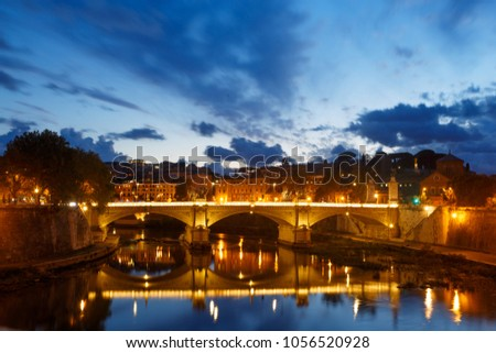 Beautiful antique bridge over Tevere river in Rome, soon after the sunset, assisting impetuously at one of the endless dates between Day and Night #1056520928