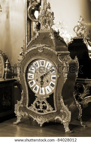beautiful antique clock on the background of the mirror