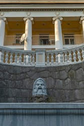 beautiful antique fountain with a sculpture of the face of an ancient god on the pediment of the building