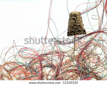 Beautiful Antique Thimble Balancing on a Needle in Front of Gorgeous Swirling Fibers