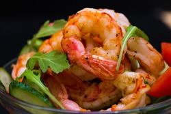 Beautiful appetizer langoustines salad, decorated vegetables cucumber and rukola.  Black background. Close up. Fried shrimps.