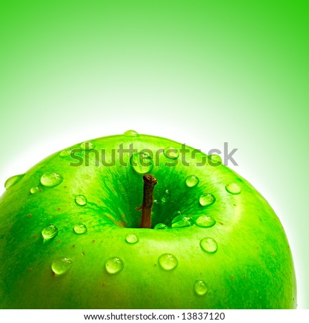 beautiful apple with droplet of water on green background