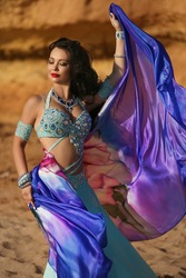 Beautiful Arabian bellydancer dancing at desert outdoor portrait. Bellydancer in jewelry at sand beach. Belly dancing. Young Turkish girl belly dance artist. Arabic woman with makeup and long hair
