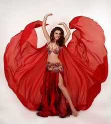 Beautiful Arabian bellydancer dancing portrait isolated on white. Bellydancer in traditional costume. Belly dancing. Young Turkish girl belly dance artist. Arabic woman with makeup and long curly hair