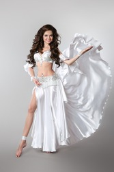 Beautiful Arabian bellydancer sexy woman in bellydance white costume over gray studio background.