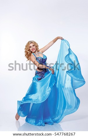 Beautiful Arabic Belly Dancer Harem Woman In Blue Dress And Jewelry Dancing Arms In Air