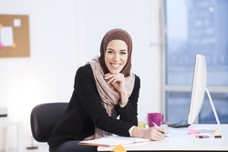 Beautiful Arabic business woman working on computer. Woman in her office,shallow depth of field