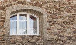 Beautiful arched window in white PVC with 3 wings in natural stone facade in granite