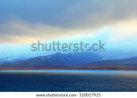 Beautiful arctic view - black mountain covered with snow and blue gulf against the background of dramatic cloudy sky near Barentsburg, Spitsbergen archipelago (Svalbard island), Norway, Greenland sea #320017925