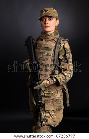 Beautiful army girl with rifle isolated on black
