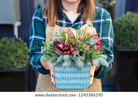 Beautiful arrangement of the natural branches of spruce and thuja, cinnamon sticks, red flowers for winter holidays decor or gift idea.