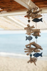 Beautiful artesian weathered handmade wood hanger souvenir with fish and driftwood from Greece. Ocean/sea vacation holiday background.  Copy space for message.