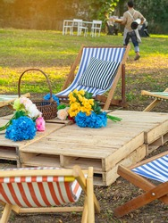 Beautiful artificial bouquets of various colors placed on wooden table among deck chairs in garden. Multi-colored artificial flowers adorn the wooden table for beautiful and relaxing. Selective focus.