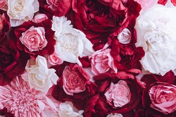 Beautiful artificial paper flowers wall pattern with amazing red, pink and white roses, peonies. Mothers Day concept background for your design. Mother's gritings card. Directly above. Copy space.
