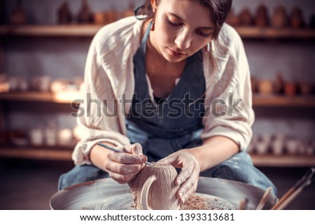 Beautiful artisan sculptor works with clay on a Potter's wheel and at the table with the tools. Handiwork.