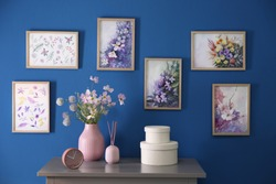 Beautiful artworks hanging on blue wall in stylish room. Interior design
