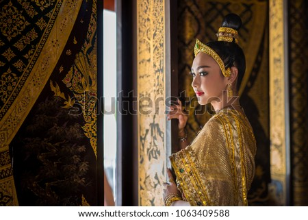 Beautiful asia woman in gorgeous antique thai dress stand near ancient gold threads old thai pattern windows in temple of Thailand.