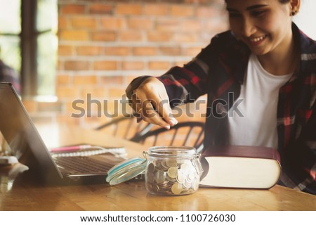 beautiful Asia woman,teen,girl putting money coins into the glass bottle for saving money with happy.