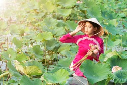 Beautiful asia women wearing white pink traditional Vietnam dress (Ao Wai) and Vietnam farmer's hat and sitting on wooden boat in flower lotus lake. Her hands holding lotus flowers.