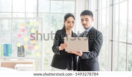 Beautiful asian business man and woman looking in laptop in office and happy.Asian business adviser meeting to analyze and discuss the situation.Investment Consultant,Financial Consultant.