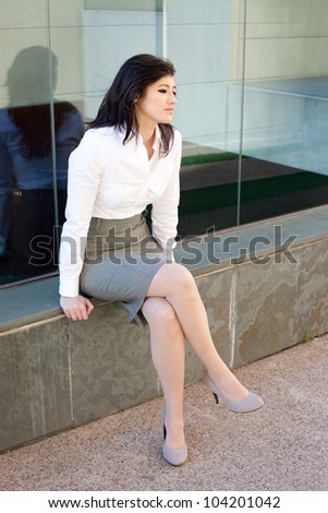 Beautiful asian business woman sitting outdoors wearing a suit.