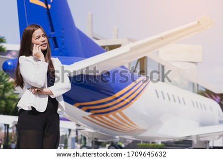 Beautiful Asian business woman smiling and talking on her smartphone while standing n front of the airplane. Business and finance concept. Foto stock ©
