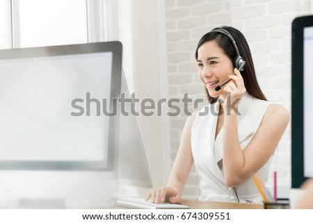 Beautiful Asian business woman wearing microphone headset working in the office as a telemarketing customer service agent, call center job concept