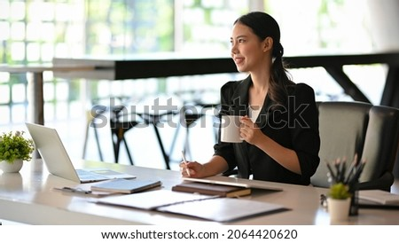 Beautiful asian businesswoman having a tasty morning coffee during work on her new project in the office.