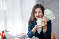 Beautiful asian businesswoman holding dollar bills and a house model. Home and land trading concept.
