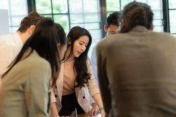 Beautiful Asian businesswoman in cream suit standing near meetingroom table with colleagues and explaining her new business plan ideas during meeting in the office meeting room.