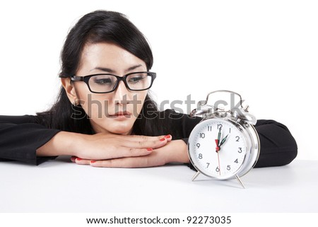 Beautiful asian businesswoman looking at alarm clock