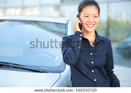 beautiful asian businesswoman on the phone leaning on car outside of office building