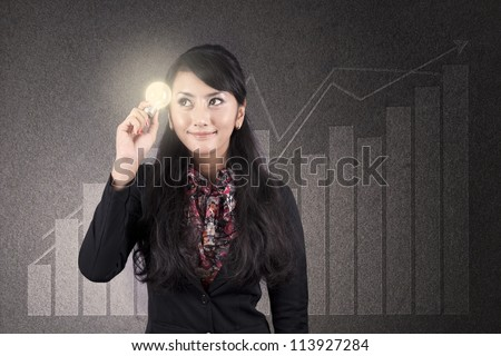 Beautiful asian businesswoman with glasses holds a light bulb over diagram background