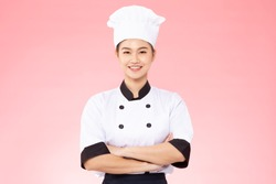 Beautiful Asian chef woman smile and cross arm isolated on pink background,Happiness and Cheerful Professional chef Concept