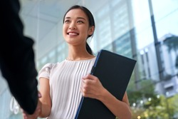 beautiful asian chinese business woman shaking hands in modern city work office