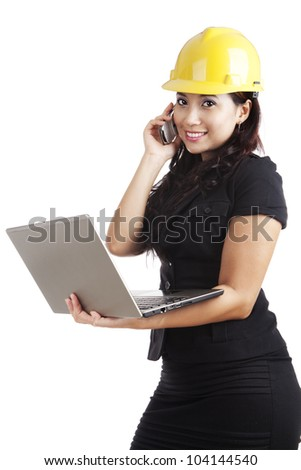 Beautiful Asian engineer holding laptop and a mobile phone