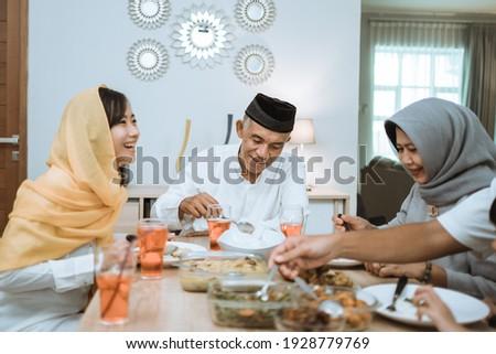 beautiful asian family enjoying their iftar dinner at home. ramadan kareem islam break fasting tradition
