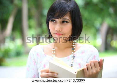 beautiful Asian female reading a book in park.