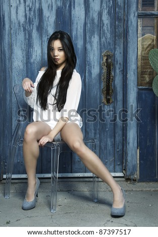 Beautiful Asian female sitting on chair with rustic background