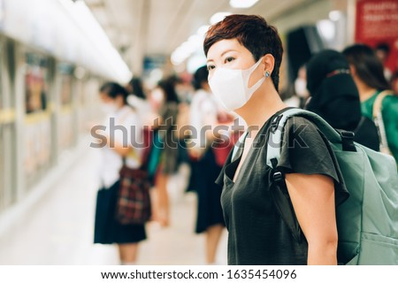 Beautiful Asian female traveller with worried look, wear medical face mask to protect from infection of viruses, pandemic, Covid-19 and epidemic of disease in crowded underground train. New normal.