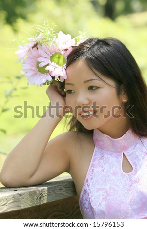 Beautiful Asian female with flowers in a summer time, park setting