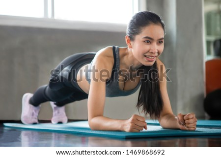 Beautiful Asian fitness young woman in sportswear doing plank in gym . sport Fit girl push up exercise in morning . healthy lifestyle concept.  workout . training. endurance . smile
