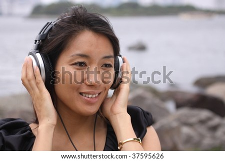 Beautiful Asian girl enjoying to music with her headphones